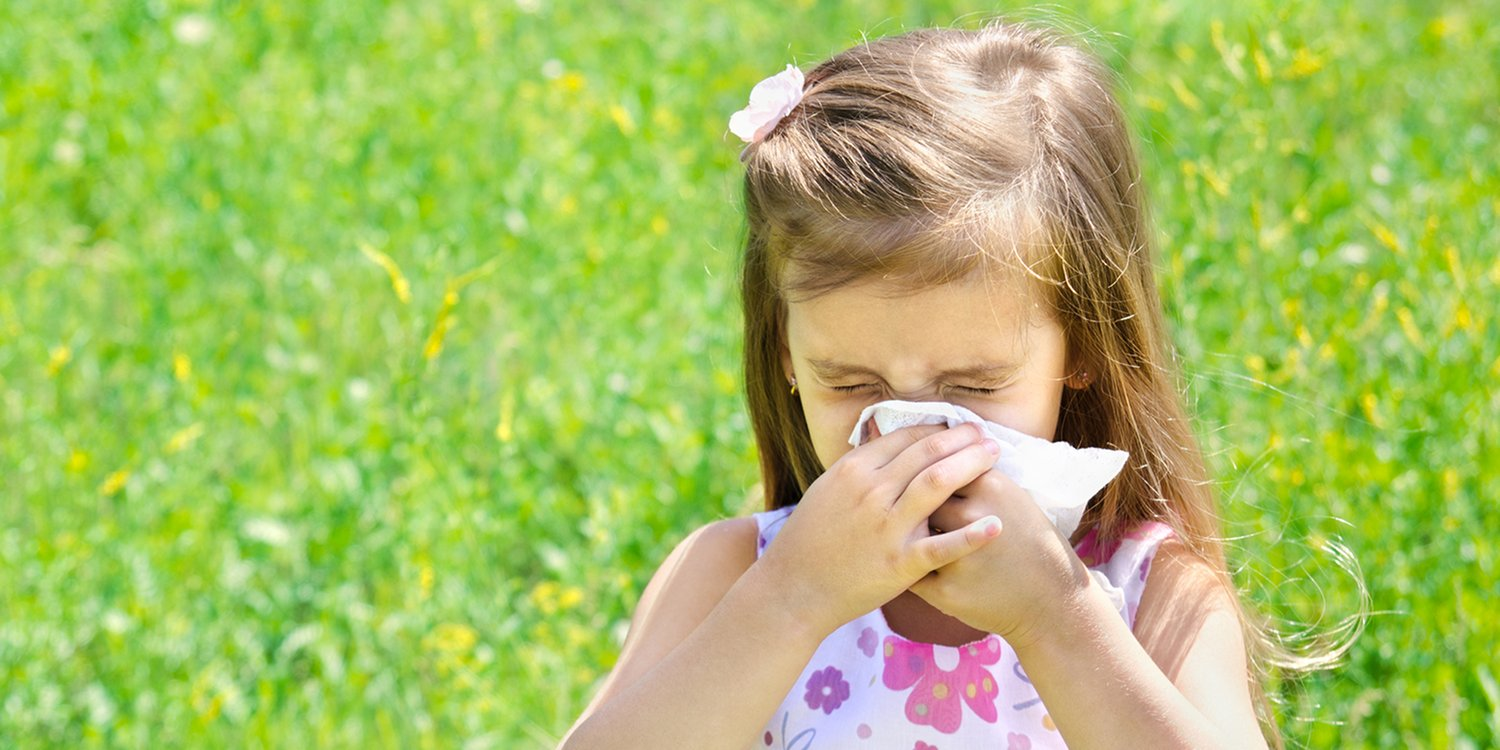 a girl sneezing in a summery field